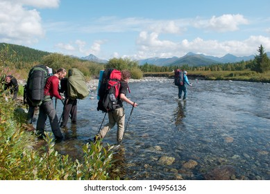 hikers crossing mountain river, Ural, Russia