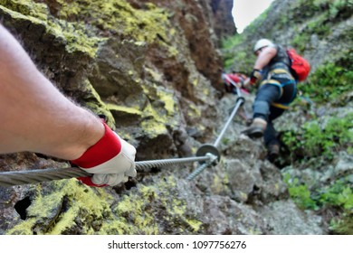 Hikers in a dangerous pathway - via ferrata in the mountain resort Skalka in Kremnica mountains- Europe, country Slovakia. Extreme hiking and climbing concept.
