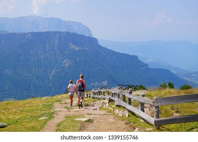 Hikers enjoy the view from an alpine ridge in the Dolomite Alps near Toblach, Italy