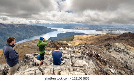 Hikers enjoy the view from the summit of Mt. Luxmore, Kepler Track Fiordland National Park, New Zealand. Lake Te Anau is visible in the distance framed by rain clouds and distance hills and mountains.