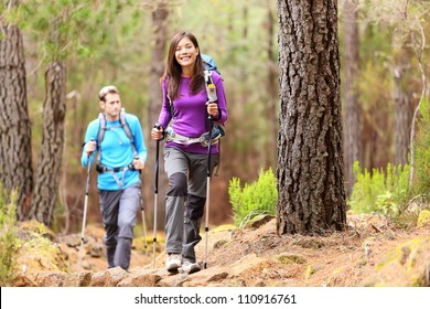 Hikers in forest. Couple hiking in fall forest. Asian woman hiker in front smiling happy. Photo from Aguamansa, Orotava, Tenerife, Canary Islands, Spain.