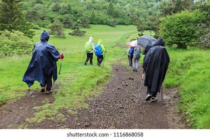 hikers group walking under the rain