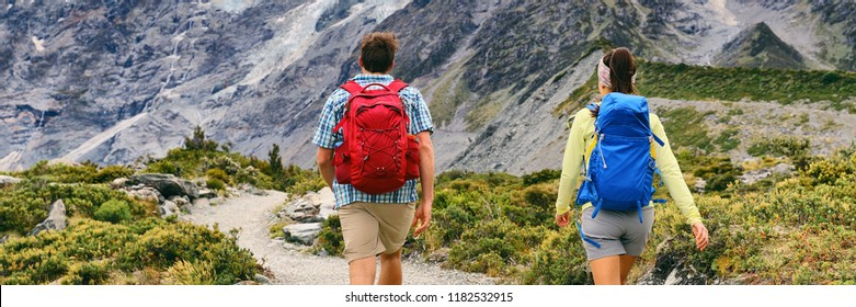 Hikers hiking with camping backpacks walking from behind with bags on outdoor trek in summer nature. New Zealand travel tramping couple on Hooker Valley Track in New Zealand mountains banner.