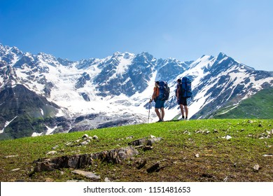 Hikers look at mountain range on a sunny summer day. Tourists in the highlands. Hiking in the mountains. Active trip to the beautiful nature. Leisure. Men on mountain trek. People in Caucasus Svaneti
