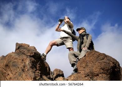 Hikers looking away through binoculars