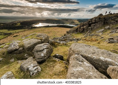 Hikers looking from hill top, adventure outdoors. Young people climbing rock formation in Dartmoor  National Park , dramatic sky and panoramic view over lake.