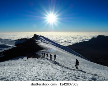 Hikers make their way to the summit of Mount Kilimanjaro on the snow