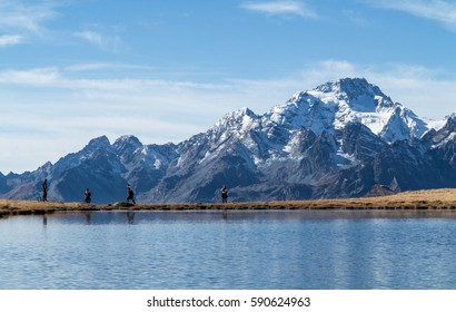 Hikers in mountain - Alpine lake and high peaks