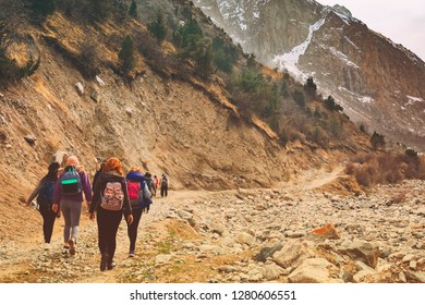 Hikers in the mountains. Group of friends or tourists walks at mountains viewpoint. Travel or tourism concept.