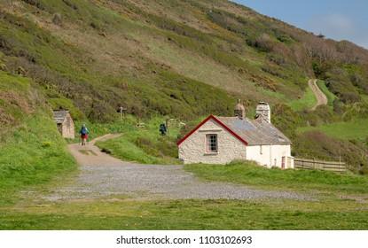 Hikers near a stone cottage on coastline near Hartland Quay on North coast of Devon