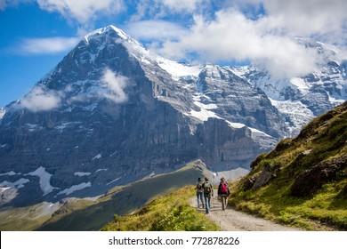 Hikers on the The Eiger trail and The Eiger, a 3,967-metre (13,015 ft) mountain of the Bernese Alps, overlooking Grindelwald and Lauterbrunnen in the Bernese Oberland of Switzerland