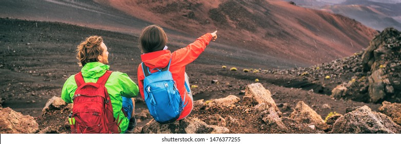 Hikers on hiking trail in volcano mountains with backpacks resting pointing at view away. Girl tourist, man traveler couple on travel adventure camping trip. Banner panorama landscape.