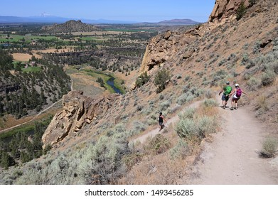 Hikers on Misery Ridge Trail in Smith Rock State Park near Terrebonne, Oregon on a cloudless summer day.