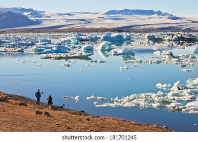 Hikers overlooking Jokulsarlon Lagoon and Vatnajokull Glacier , Iceland