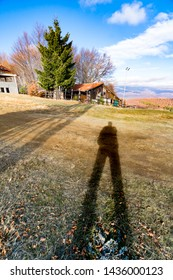 Hiker's own shadow on the meadow at mountain summit with wooden hut, vertical