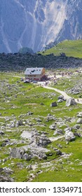 Hikers pass aan alpine hut on the way to the  Drei Zinnen area of the  Dolomites Alps, Italy
