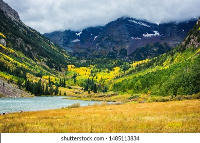 Hikers Pass Alpine Lake at the Maroon Bells