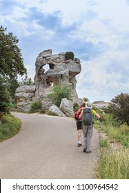 hikers passing near a rock