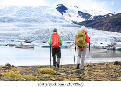 Hikers - people on adventure travel on Iceland. Hiking man man woman walking to glacier and glacial lagoon / lake of Fjallsarlon, Vatna glacier, Vatnajokull National Park. Couple in active lifestyle.