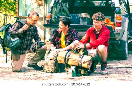 Hikers preparing backpack behind pickup truck - Best male friends ready for trekking day - Young people setting camping equipment - Concept of adventure , friendship ,travel and outdoor activities