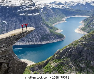 Hikers raising hands on Trolltunga rock enjoying the view of the amazing fjord, nature landscape, Norway. Concept of success, freedom and happiness