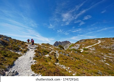 Hikers reaching the summit of a ridge with Cradle Mountain in background (Tasmania)