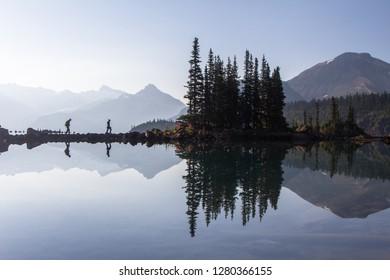 Hikers reflect in the water of Garibaldi Lake in British Columbia, Canada