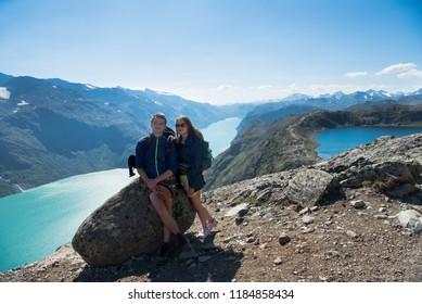 hikers resting on stone on Besseggen ridge over Gjende lake in Jotunheimen National Park, Norway