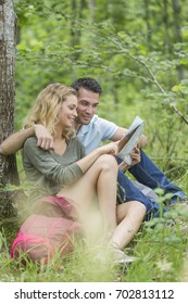 Hikers sat under a tree reading a map
