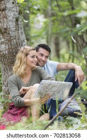 Hikers sat under a tree searching the way with a map