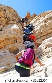 hikers scrambling up rock wall