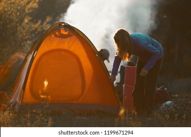 Hikers set the tent and make fire in the wild area