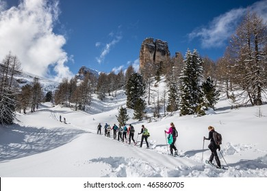Hikers snowshoeing below bastion mast formation of Cinque Torri between rocky mountain peaks of the Dolomites, Italian Alps at sunset in wintertime