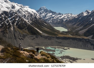Hikers taking in the view from the top of the Tarns Track up the Hooker valley to Mount Cook, Mueller Lake in the foreground. Aoraki/Mount Cook National Park, New Zealand.