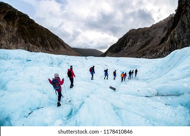 Hikers and travelers walking on ice in Fox Glacier, New Zealand. Breathtaking guided glacier walk onto the world-famous Fox Glacier. This is a famous place and popular activity in the south island.