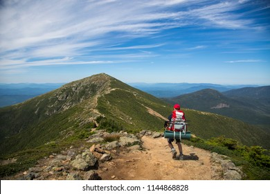 Hikers trekking along a mountain range, the Franconia ridge traverse, with a beautiful landscape background and blue skies on a sunny day. Mount Lafayette, Mount Lincoln, New Hampshire, America