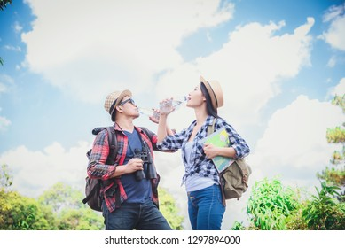 Hikers walk up the mountain, take a break, and drink bottled water.