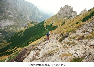 Hikers walking along a trail in rugged mountain terrain