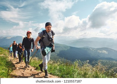 hikers walking by the trail in the mountains. Active hikers climb the path in the mountains with beautiful cloudy sky on background, travel and outdoor adventure concept. Carpathians, Ukraine