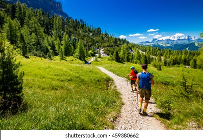 hikers walking on mountainous trail. Summer Trekking in Dolomites.