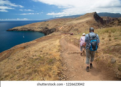 Hikers walking over the rough and rocky vulanic coastline of madeira Island with steep cliffs