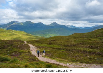 Hikers walking in Scottish mountains on West Highland Way.