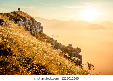 hikers walking at sunrise on top of italian alps mountains - weekend activities vacation and sport concept with adventure people - Warm bright sunshine filter