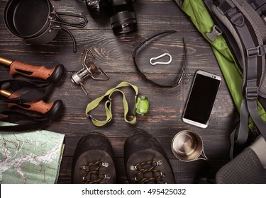 Hiking accessories. Boots, backpack, sunglasses, photo camera, map, smartphone, flashlight and others. Top view.