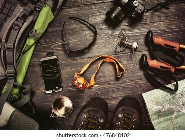 Hiking accessories set on dark wooden background:  boots, backpack, sunglasses, photo camera, map, smartphone, flashlight and others. Top view. Vintage retro effect
