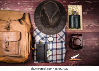Hiking accessories with shirt, hat and backpack on wooden planks