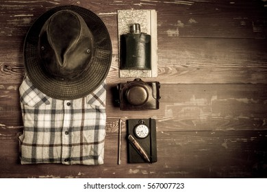 Hiking accessories with shirt and hat on wooden planks in sepia filter