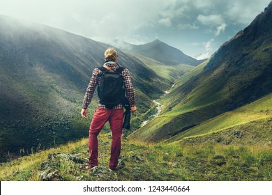 Hiking Adventure Blogger Travel Concept. Handsome Male Traveler With A Beard And Digital Camera Enjoying Summer Mountain View, Rear View