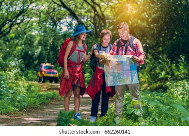 Hiking and Adventure in forest - Asian hikers looking at map. Couple or friends navigating together keep smiling happy during camping travel hike outdoors in forest. Young mixed race woman and man.