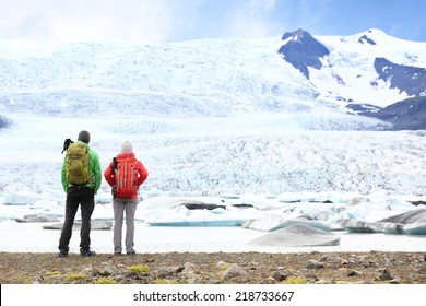Hiking adventure travel people on Iceland. Hikers looking at glacier and glacial lagoon / lake of Fjallsarlon, Vatna glacier, Vatnajokull National Park. Couple visiting Icelandic nature landscape.